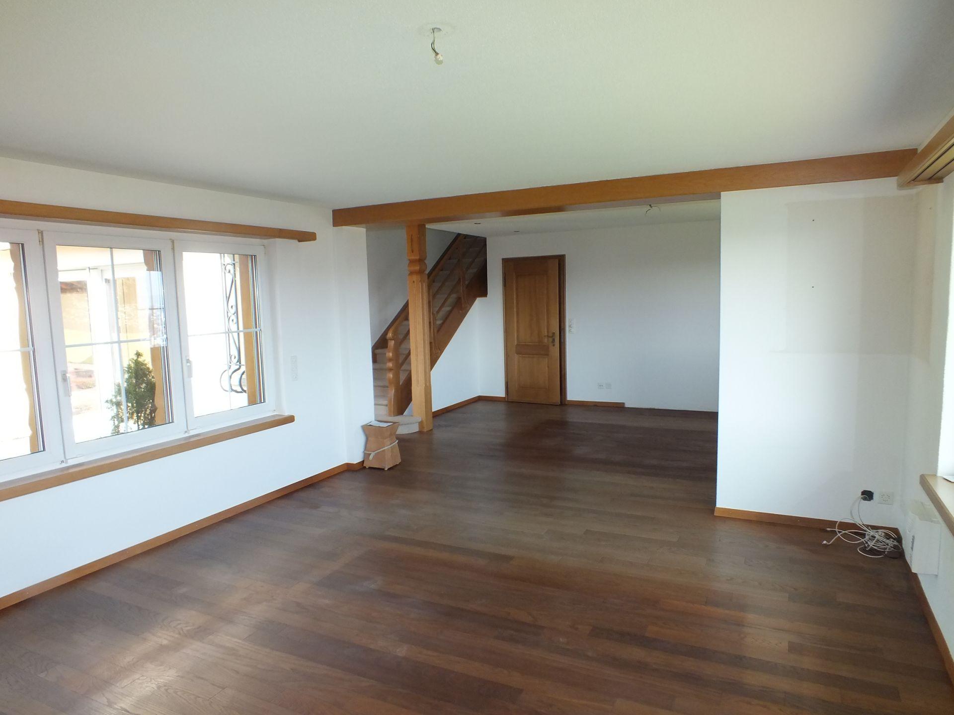 Wohnzimmer mit Blick Richtung Eingangshalle und Treppe ins Obergeschoss